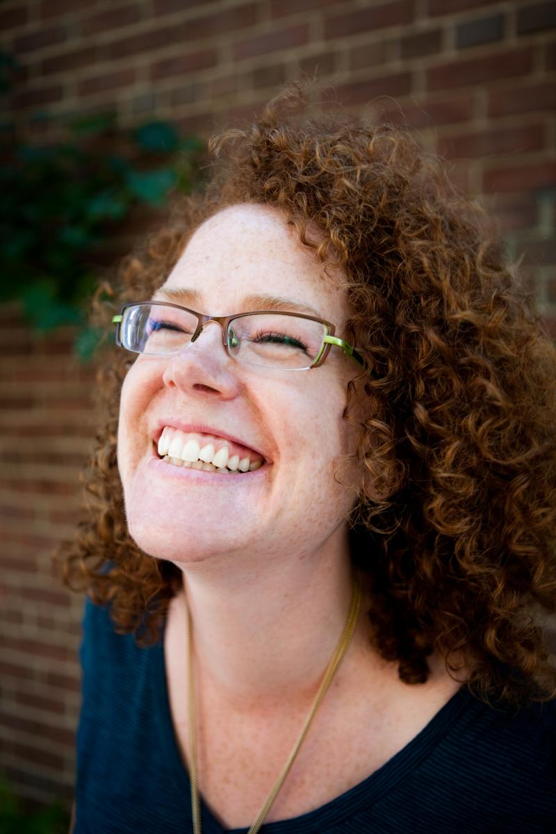 Melanie McNeill. A mid aged white woman with light brown hair in tight curls that go to her shoulders. She's wearing glasses and smiling wide.