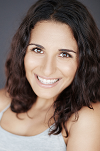 Michaela Di Cesare. A woman with light skin and long brown hair and brown eyes. She is smiling.